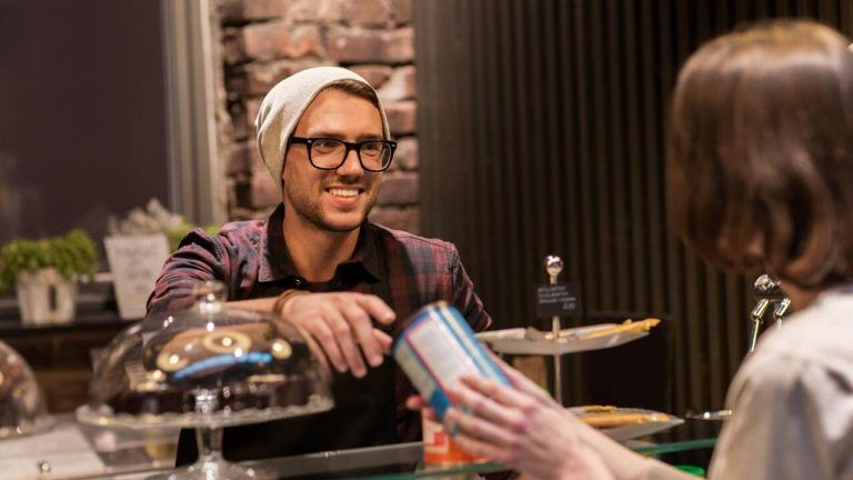 man serving customer cafe smiling great customer service